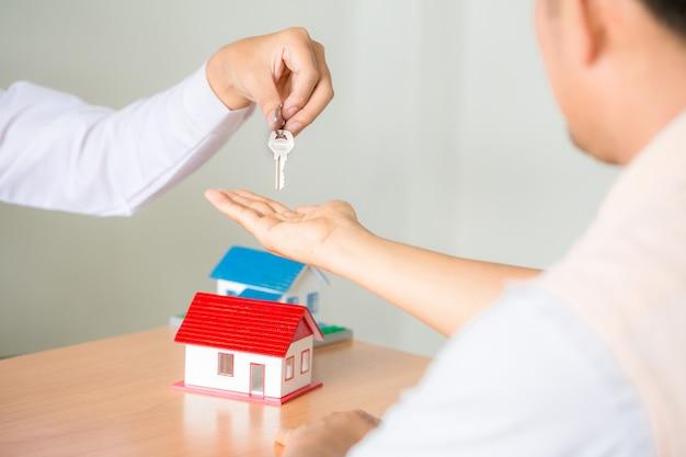 Onroerend goed verkoopmanager die sleutels geeft aan klant na ondertekening huurleasecontract of verkoopaankoopovereenkomst