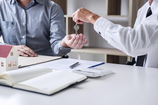 Onroerend goed verkoopmanager die sleutels geeft aan klant na ondertekening huurleasecontract