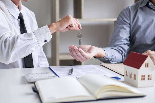 Onroerend goed verkoopmanager die sleutels geeft aan klant na ondertekening huurovereenkomst verkoopovereenkomst voor verkoop