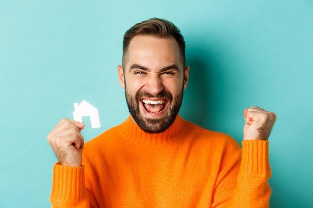 Onroerend goed. vrolijke man koopt appartement, verheugt zich en zegt ja, toont klein papieren huisje, staande over lichtblauwe achtergrond.