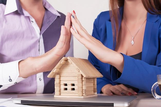 Onroerende goederen en bezitsconcept - sluit omhoog van handen houdend huis of huismodel