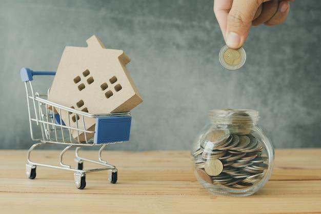 Onroerende goederen en het kopen en verkopen van huisconcept, hand gezet geldmuntstuk in kruik en huismodel in kar