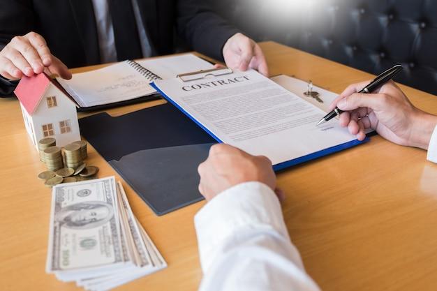 Onroerende goederenagent die huissleutels geeft het teken van de klant ondertekeningsbezit voor verkoop