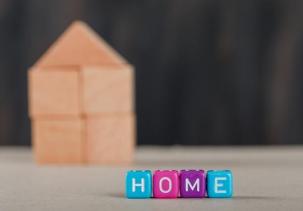 Onroerende goederenconcept met gekleurde kubussen, houten huis en wit.