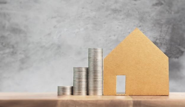Onroerendgoedinvestering en het financiële concept van de huishypotheek, hand die het huis van het geldmuntstuk zetten