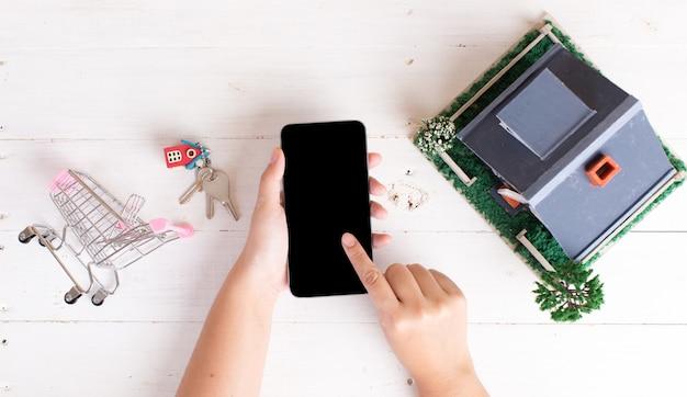 Onroerendgoedmarkt met huissleutels, winkelwagentje en telefoon