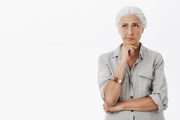 Onrustige, bedachtzame oudere vrouw met grijs haar, die peinzend linksboven kijkt