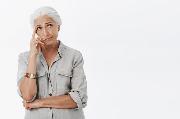 Onrustige, bedachtzame oudere vrouw met grijs haar, die peinzend rechtsboven kijkt