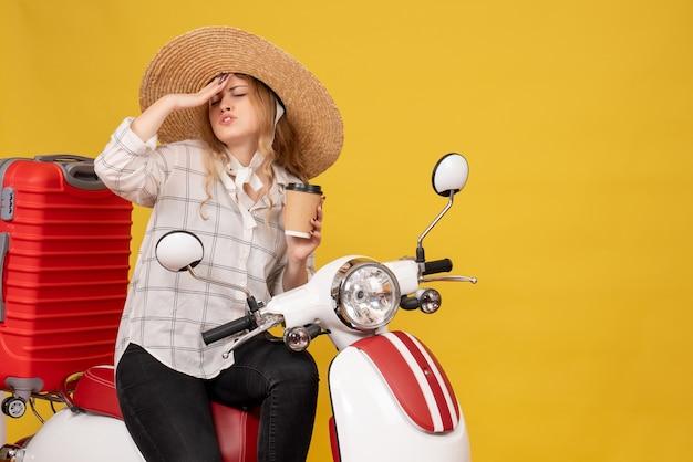 Onrustige jonge vrouw die hoed draagt en aan hoofdpijn zittend op motorfiets lijdt en kaartje toont