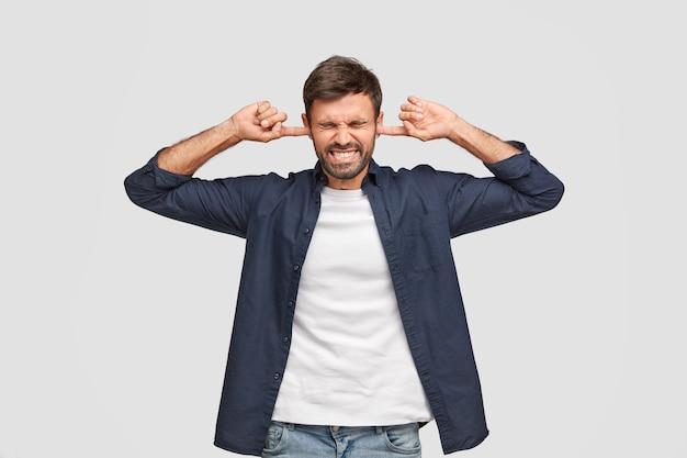 Onrustige man van middelbare leeftijd stopt oren met ontevreden uitdrukking, klemt zijn tanden