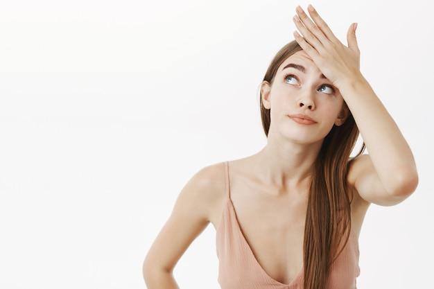 Onrustige mooie blanke vrouw in beige avondjurk die de hand op het voorhoofd houdt en omhoog gluurt met een intense gehoorde grijns die ontevreden is over vermoeiende taken over grijze muur