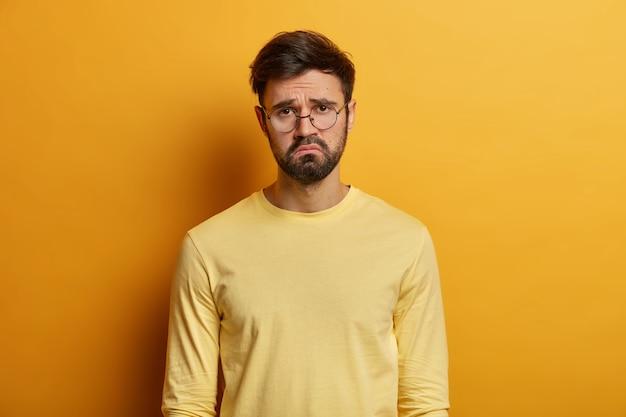Onrustige, ontevreden, bebaarde man fronst zijn wenkbrauwen, voelt zich verdrietig, bedroefd en overstuur, verveeld zittend in quarantaine, ongelukkig om een goede kans te missen, nonchalant gekleed, geïsoleerd over gele muur.