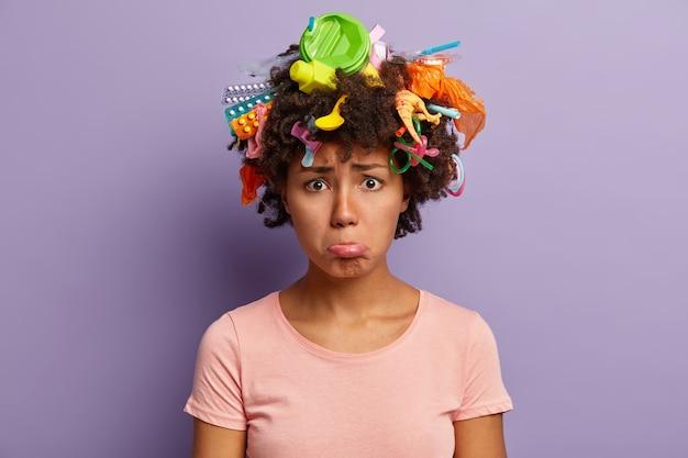 Onrustige ontevreden dame portemonnees onderlip, verzamelt plastic afval, draagt casual t-shirt, is milieuvriendelijk, boos door ernstig milieuprobleem, heeft afval in krullend haar geïsoleerd op paarse muur