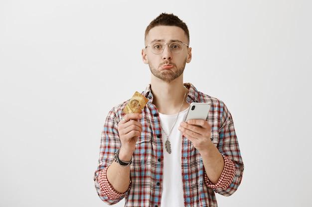 Onrustige sombere jonge kerel met een bril poseren met zijn telefoon en kaart