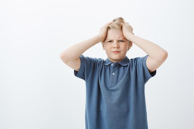 Onrustige sombere schattige jongen met blond haar, hand in hand op het hoofd en starend met een ontevreden uitdrukking opzij, fronsend