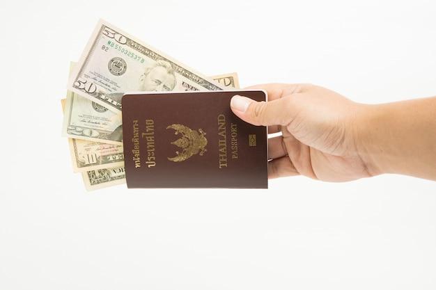 Ons die dollar in het paspoort van thailand op hand op witte achtergrond wordt geïsoleerd.