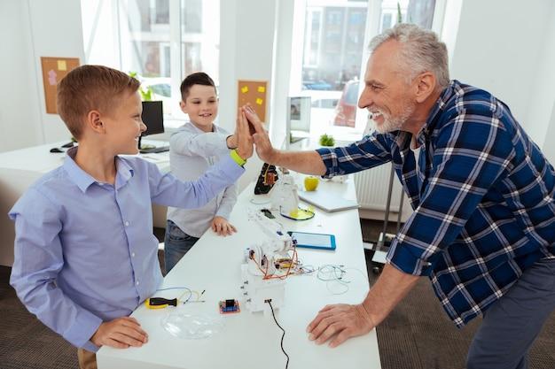 Ons succes. gelukkige bejaarde man die naar zijn leerling kijkt terwijl hij hem een high five geeft