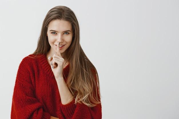 Ons vuile kleine geheim. studio-opname van blije goed uitziende blanke vriendin in rode losse trui, die shh zegt met shush-gebaar, wijsvinger over mond houdt en flirterig over grijze muur glimlacht
