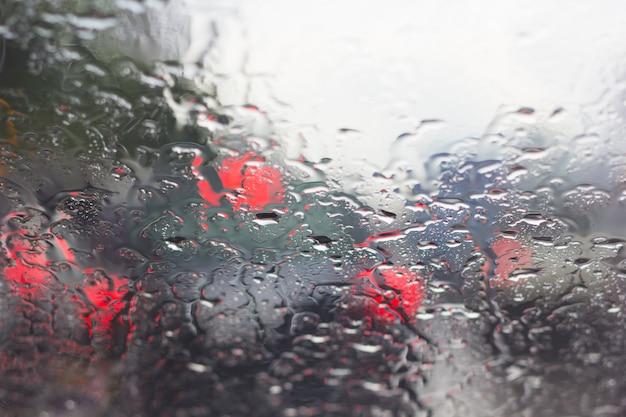 Onscherp autosilhouet dat door waterdalingen wordt gezien op het autowindscherm