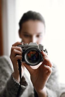 Onscherp meisje met fotocamera in haar handen op bank dichtbij venster