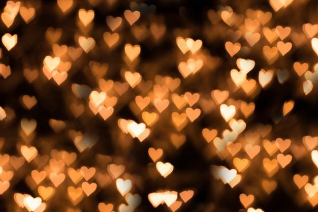 Onscherpe achtergrond, bokeh in de vorm van een hart van gele warme kleur.