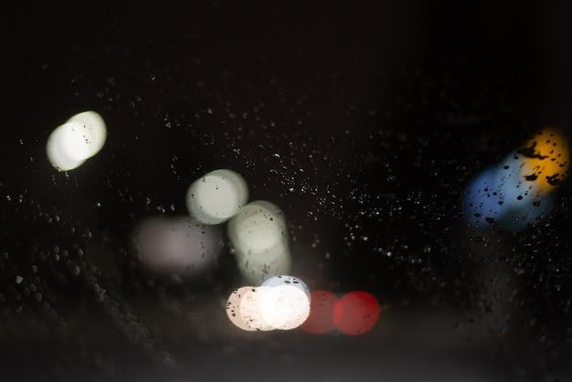 Onscherpe achtergrond met regendruppels en lichten.