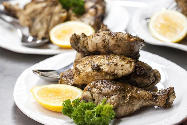 Onscherpe achtergrond van gebakken kip met citroen op witte plaat in het restaurant.