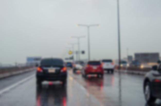 Onscherpe achtergrond van verkeer op de weg als het regent