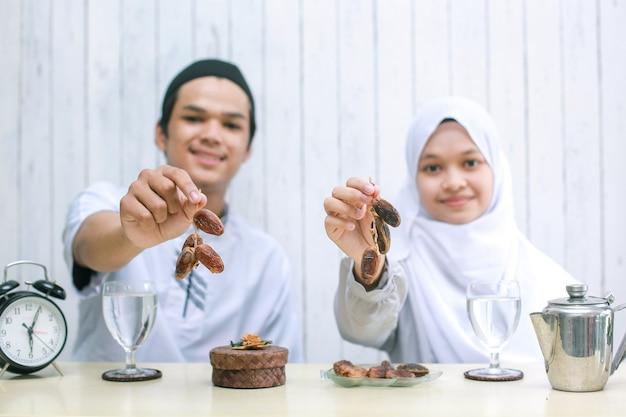 Onscherpe foto van moslimpaar dat en dadels bij de hand in de camera glimlacht aanbiedt