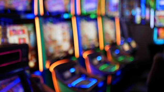 Onscherpe gokautomaten gloeien in het casino van las vegas, vs. verlichte neon gokautomaten.