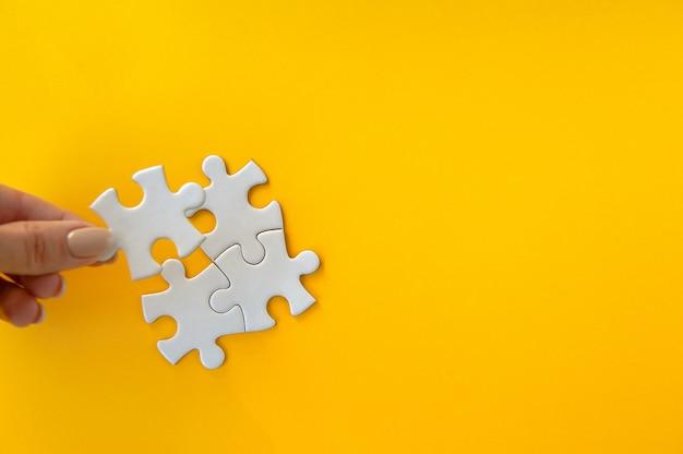Onscherpe hand die raadselstuk op oranje achtergrond probeert te verbinden. kwartair stuk platte puzzel.
