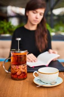 Onscherpe vrouw met notitieboekje en gezonde thee op zakenlunch