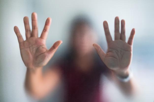 Onscherpe vrouwenhand achter de berijpte metafoorpaniek van het glasglas en negatieve donkere emotioneel