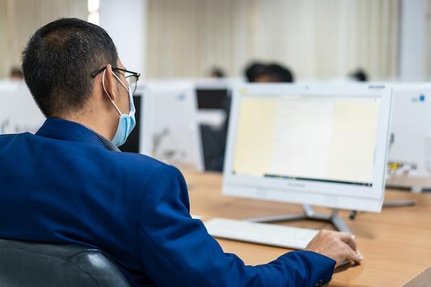 Onscherpte en selectieve focus van de volwassen universitaire studenten die een gezichtsmasker dragen terwijl ze zich concentreren op het online onderzoek in de computerruimte. serieuze studenten die aan de computer werken op de universiteit