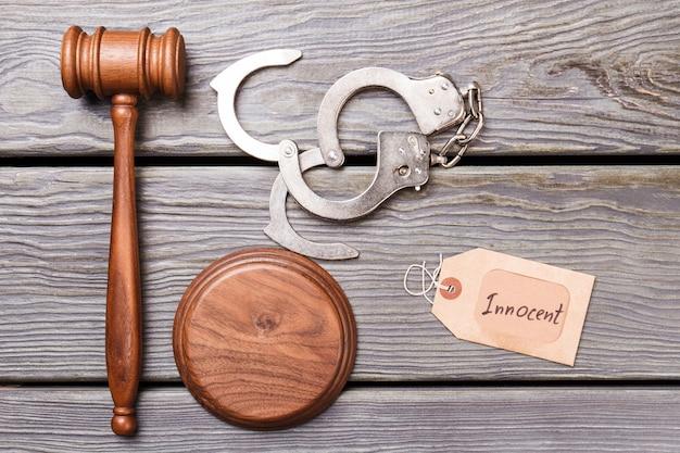 Onschuldig oordeel concept. hamer en handboeien op houten bureau.