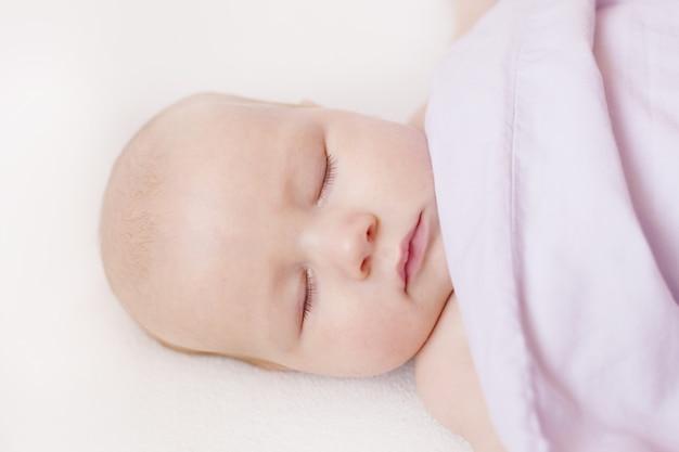 Onschuldig slapend babygezicht, bedekt met deken, zoete babydromen