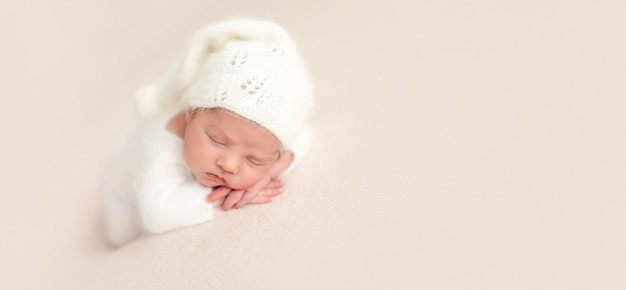 Onschuldige pasgeboren engel in wit gebreid pak