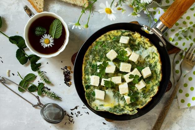 Ontbijt achtergrond gebakken eieren met spinazie feta kaas op stenen tafel top view