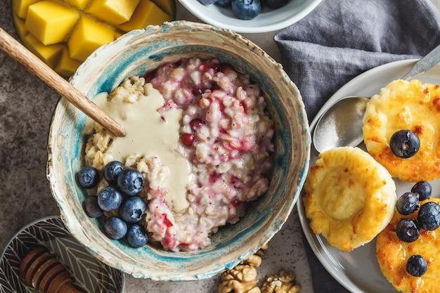 Ontbijt achtergrond. havermout, kwark pannenkoeken met bessen en fruit op donkere achtergrond.