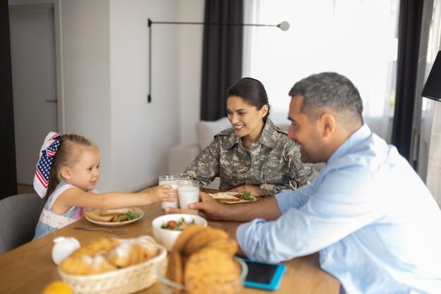 Ontbijt allemaal samen. gelukkig stralende familie die hun glazen met melk rammelt terwijl ze allemaal samen ontbijten