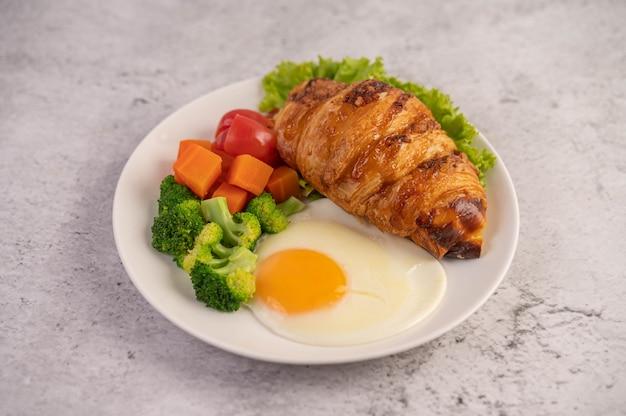 Ontbijt bestaande uit brood, gebakken eieren, broccoli, wortelen, tomaten en sla op een witte plaat.