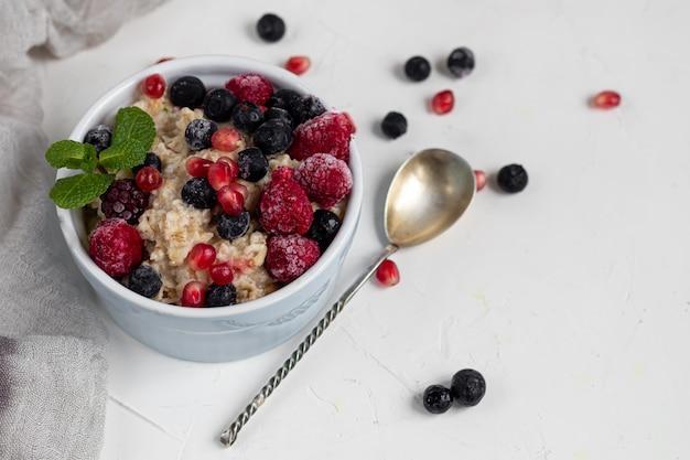 Ontbijt bestaande uit havermout, noten en fruit. kiwi frambozen bramen granaatappels amandelen munt versieren een bord.