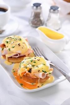 Ontbijt. beste eggs benedict. gebakken engels broodje, ham, gepocheerde eieren en heerlijke hollandaise botersaus