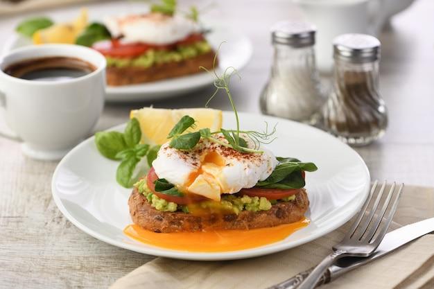 Ontbijt. beste eggs benedict op een sneetje geroosterd ontbijtgranenbrood met guacamole en spinazie