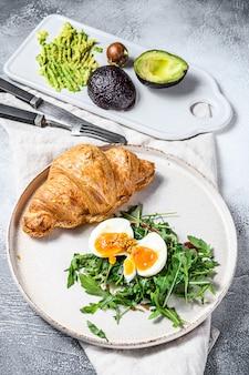 Ontbijt, brunch met avacado, rucola, croissant en ei. bovenaanzicht