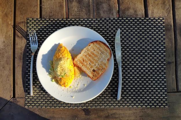 Ontbijt buitenshuis een omelet op een witte plaat vork en mes op de houten tafel