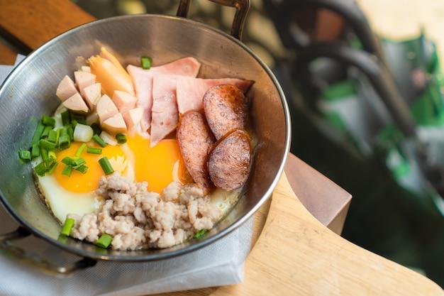 Ontbijt dat bestaat uit gebakken ei, worst, ham en gehakt varkensvlees in een kleine pan