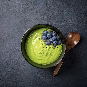 Ontbijt detox groene smoothie kom van banaan en spinazie op zwarte ondergrond