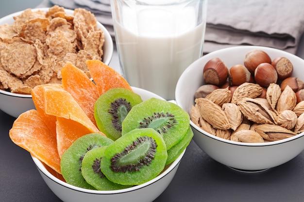 Ontbijt. drie kommen met noten, cornflakes, gedroogde kiwi en mango. een glas melk. gezond eten.