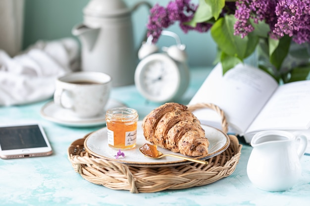 Ontbijt franse croissant, jam, kopje koffie, melk en room en lila bloemen.